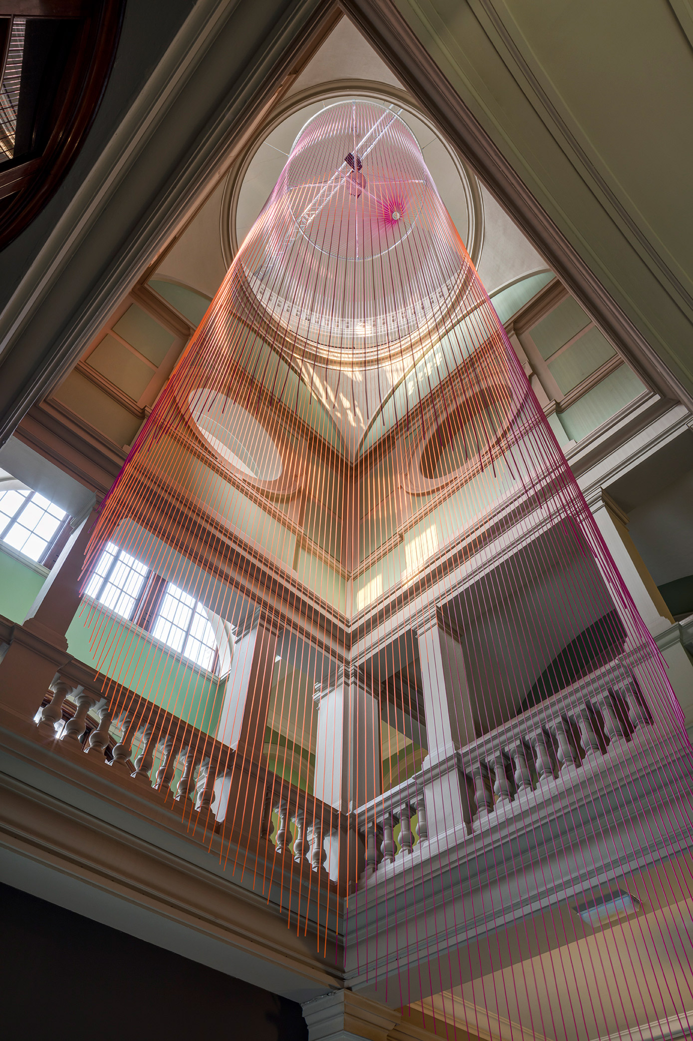 The Green Room is a kinetic installation that was designed for a six storey stairwell at the Victoria and Albert Museum. Suspended from the ceiling above, a curtain barrel of multicoloured silicon cords moves slowly in a wave like motion creating an ever changing kaleidoscope of colour.