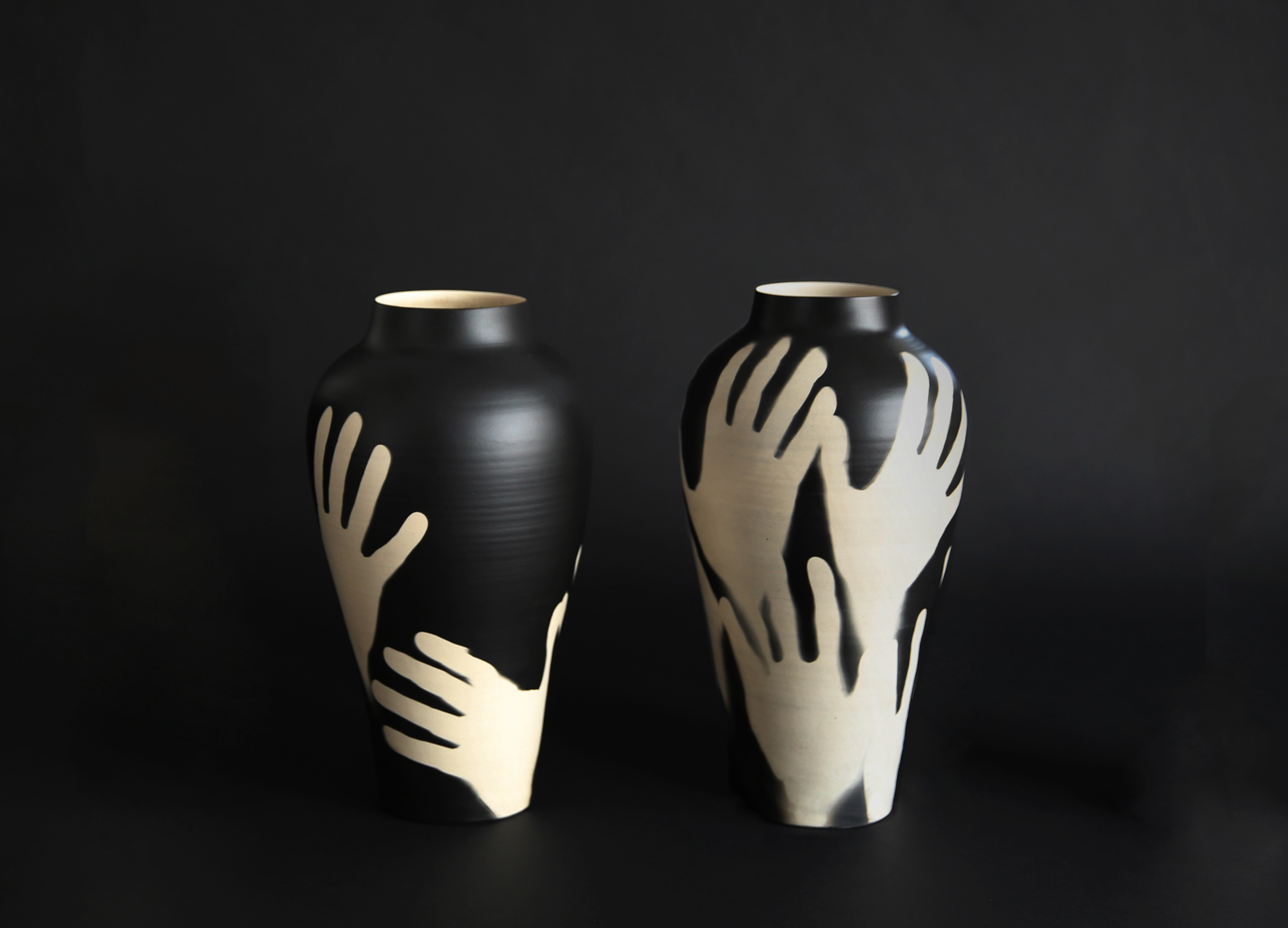 Hold Me is a collection of vases with silver gelatin photograms. The hands depicted on the pieces are achieved using an original photographic process, whereby light-sensitive vases are revolved within a shard of light.