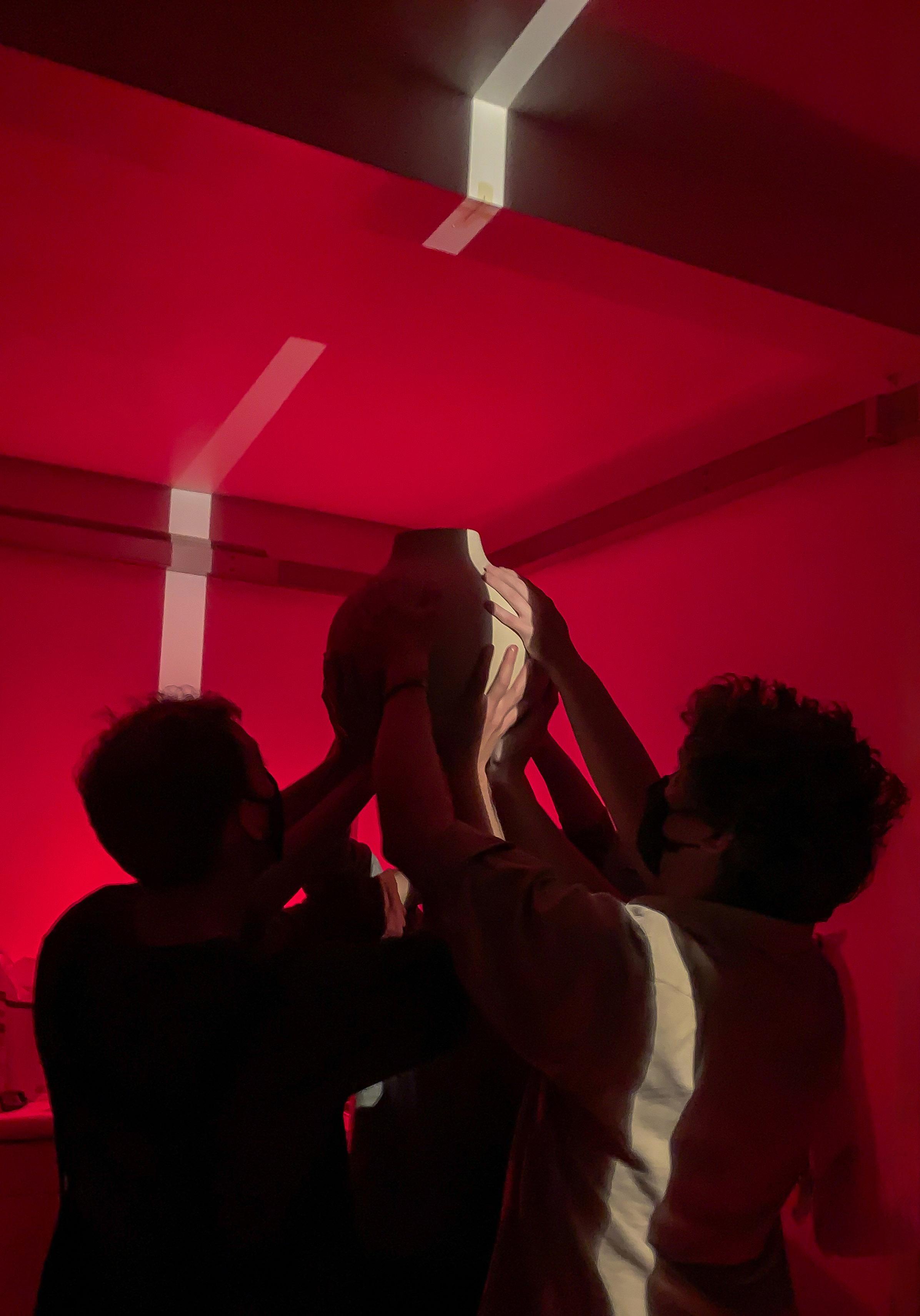People holding vases in the darkroom