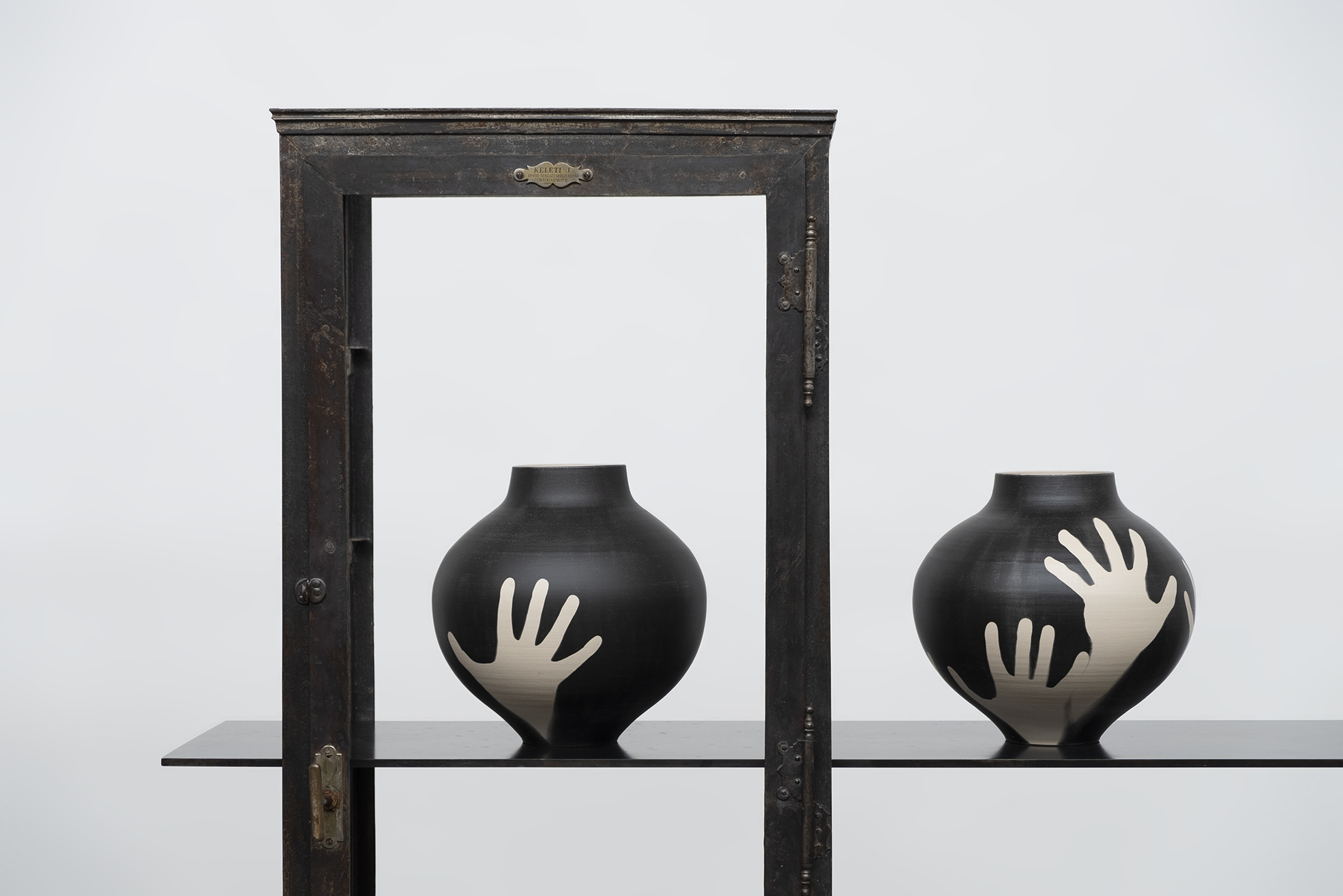 Two Hold Me vases placed on furniture by James Plumb