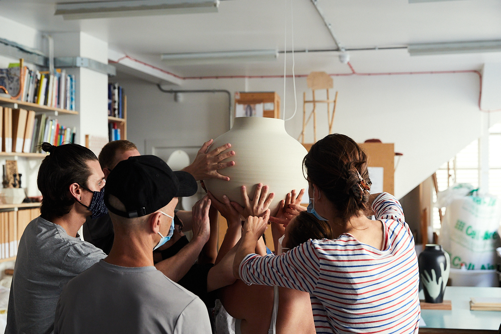 A team rehearsing the making of a Hold Me vase in the studio