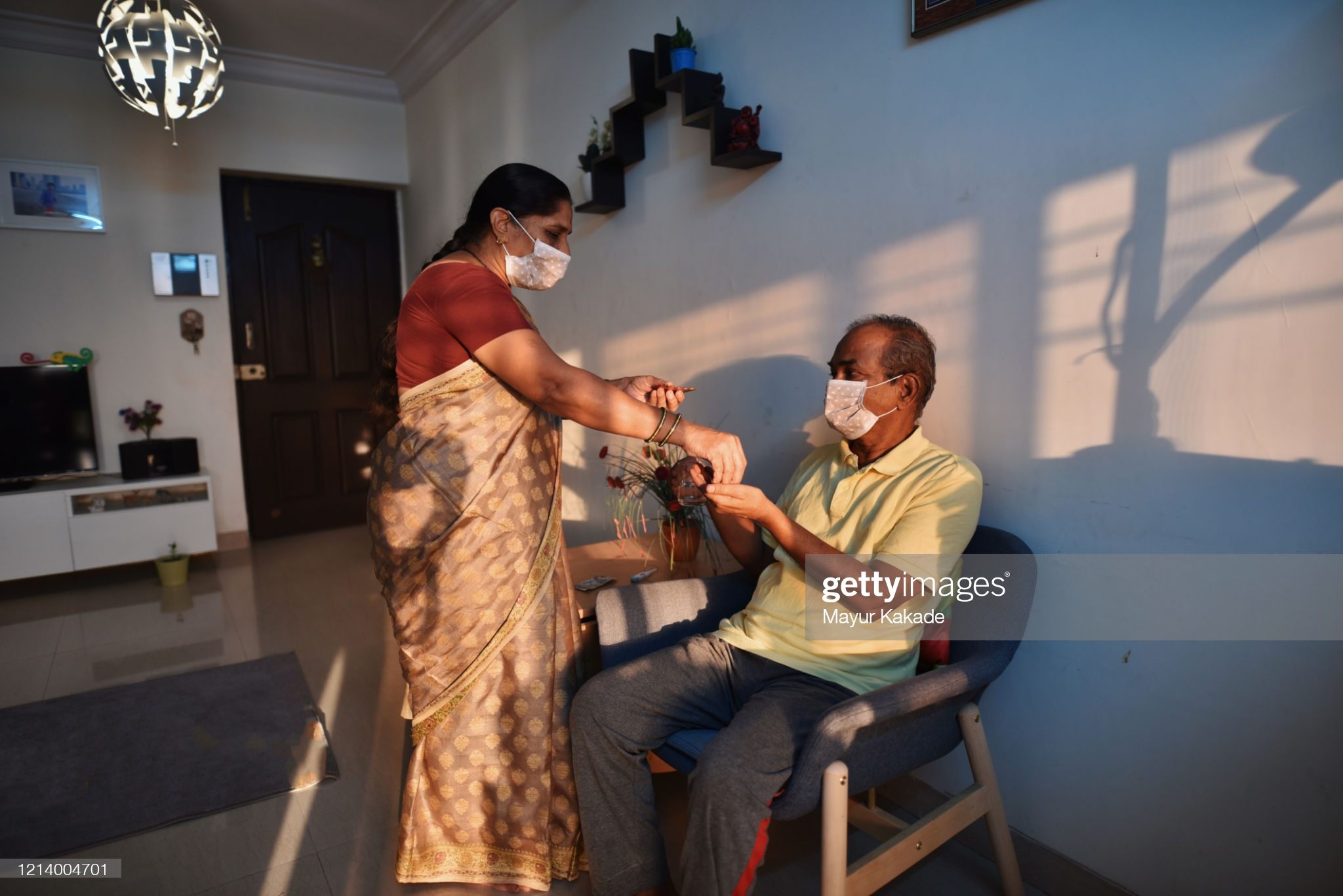 Senior woman wearing medical mask giving medicine to husband : Stock Photo