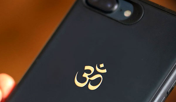 Gold plated metallic sticker of the Om syllable