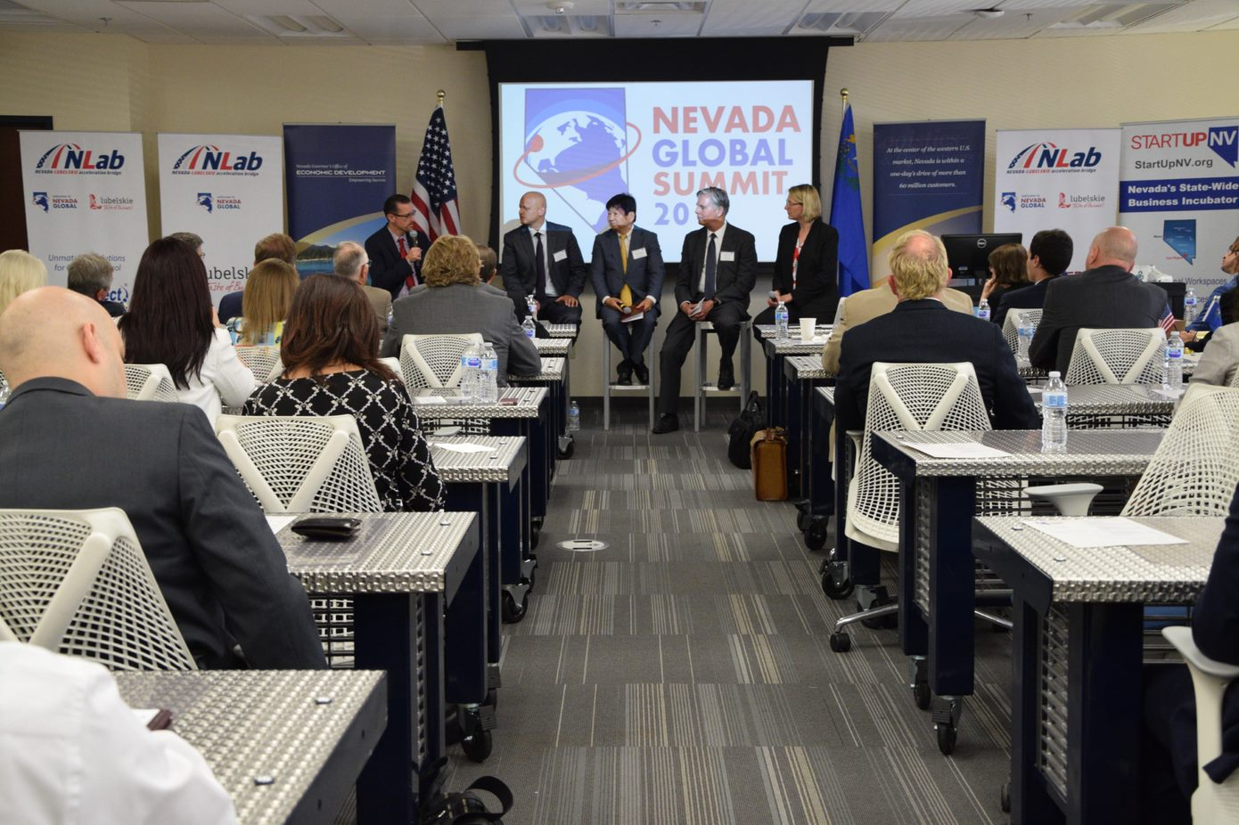 Polish Business and Innovation Week in Nevada. People sitting on the desks like in the school, in front of them are sitting five people on the tall bar chairs, one of them is the host.
