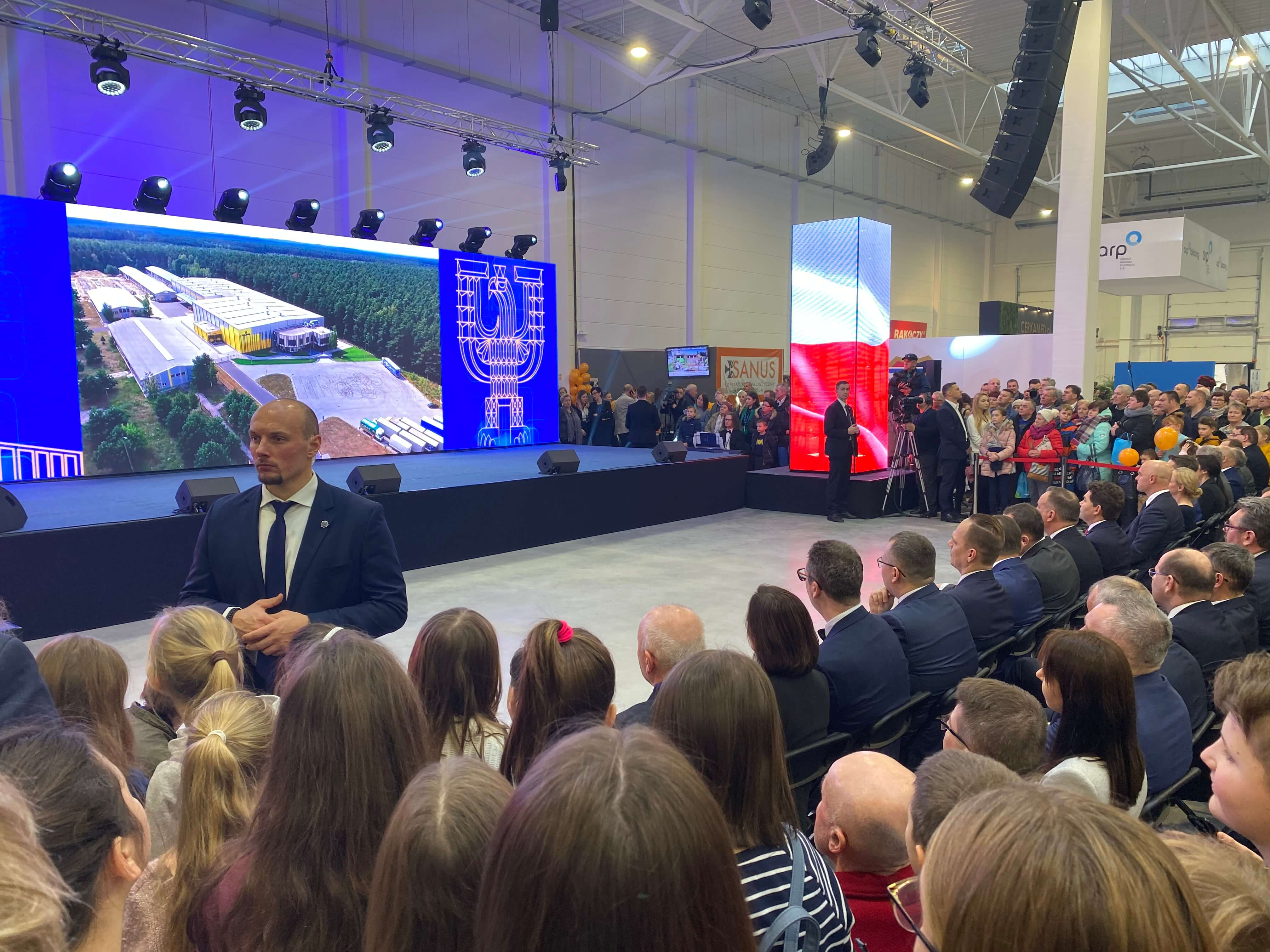 People sitting in fron of the scene with a big screen on the Polish Economic Exhibition 2020.