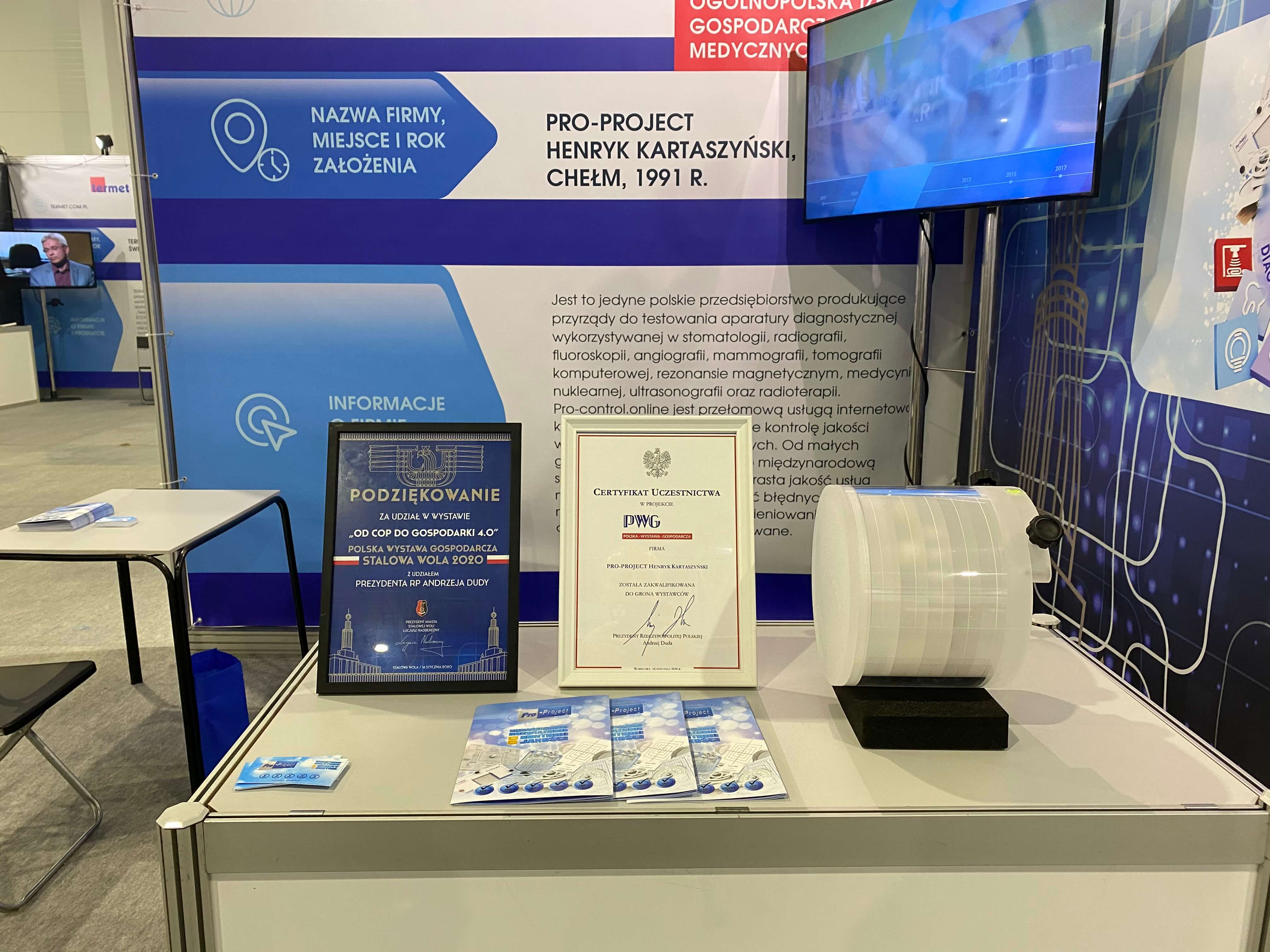Pro-Project's booth on the Polish Economi Exhibition 2020. A square space with big TV, and a table. On the table are flyers, Pro-CT MK II phantom and certyficates.