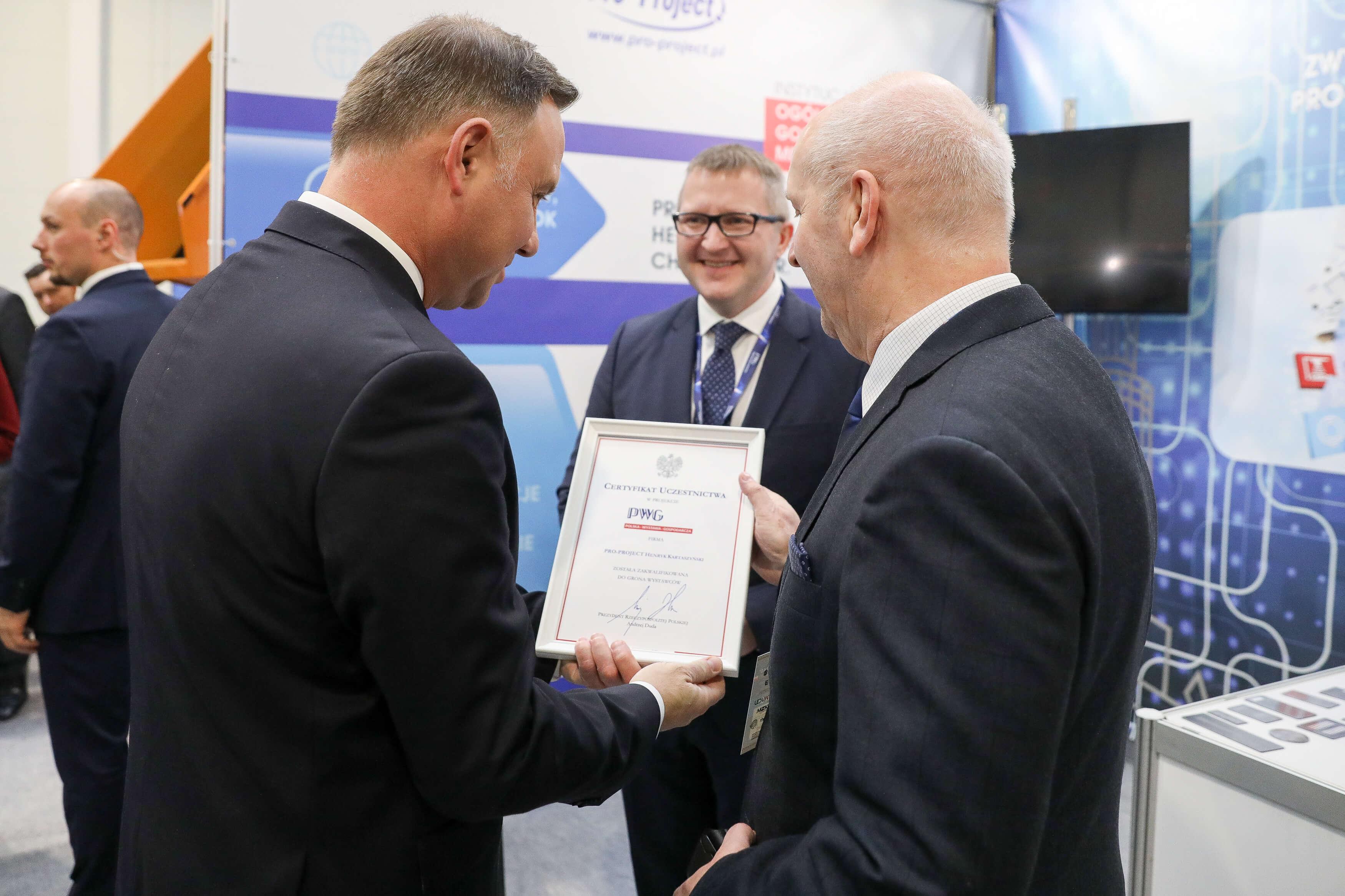 Polish president is handing the certiicate to Henryk Kartaszyński.