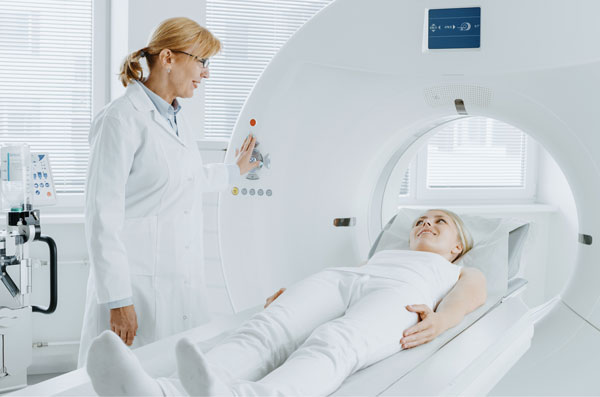 Female doctor is standing over the female patient, the patient lies on the bed of CT machine. Both are dressed white.