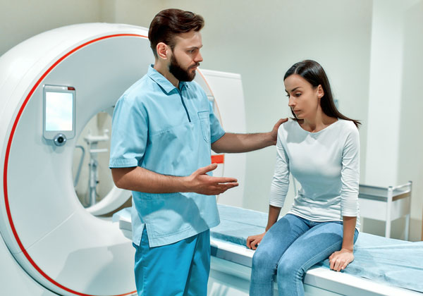 Male nurse is explaining something to a female patient, the patient is sitting on the bed of a MRI machine.