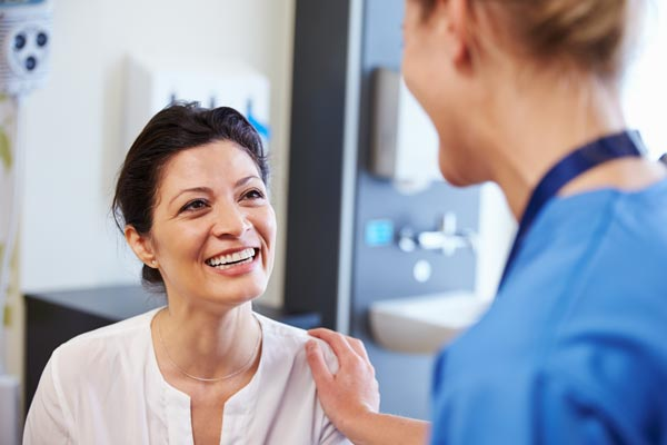 Nurse is comforting female patient, both are smiling.