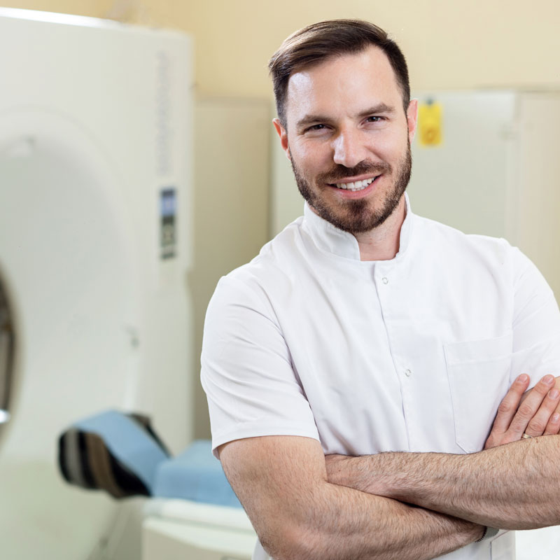 A smiling man standing in front of magnetic resonance machine.