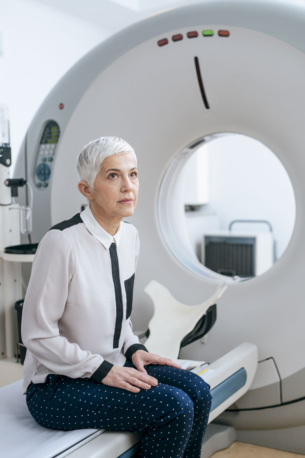 Older woman with short hair sitting on the bed of a tomograph, waiting looking up at somebody.