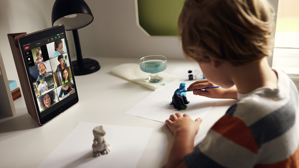 A child using the new iPad while painting a figurine.