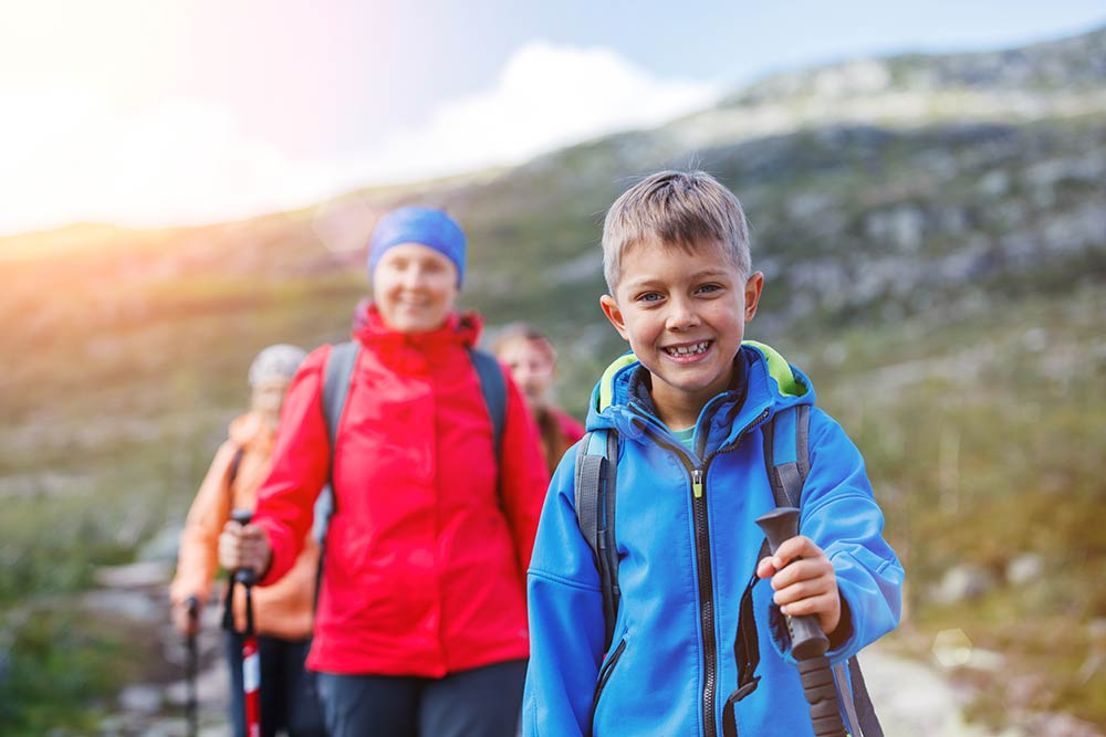 Hiking boy in the mountains smiling
