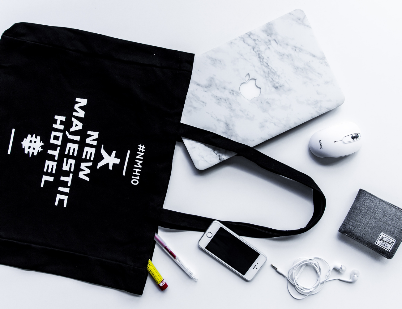 Branded merch and tote bag with laptop and electronic accessories.