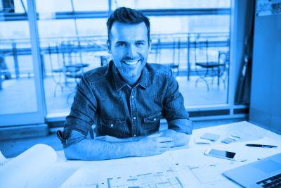 Blue duotone image of architect sitting at a desk.