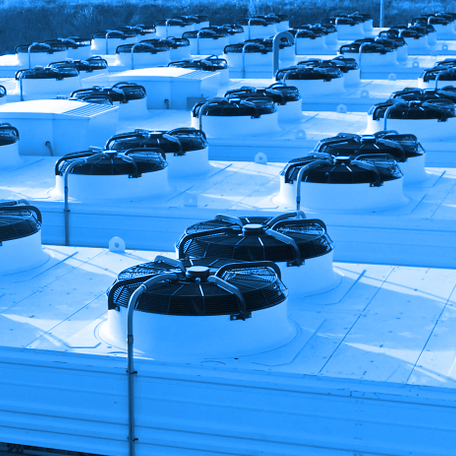 Blue duotone image of fans on a building roof.