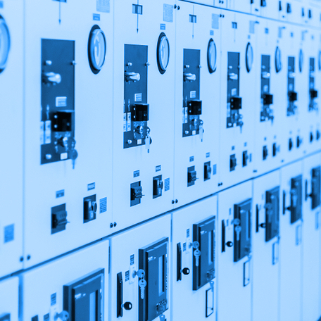 Blue duotone image of electrical panels with switches and gauges.