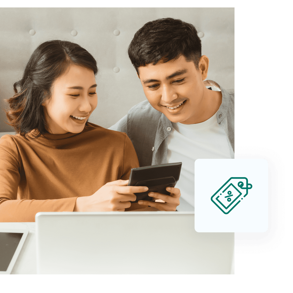 Young Asian couple smiling, looking at their finances.