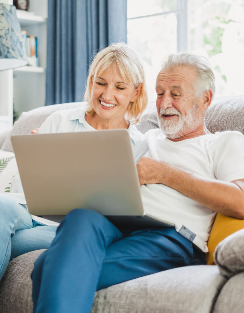 An older couple relaxing on the couch, smiling at their computer.