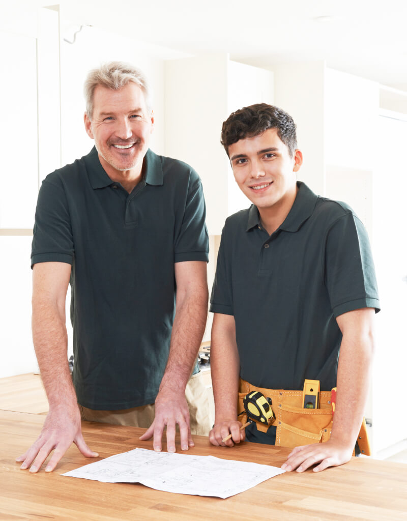 Two tradies smiling at the camera.