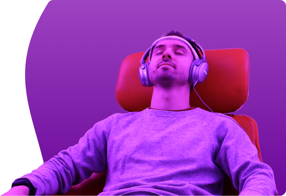 young man is listening to music in headphones relaxing in red chair