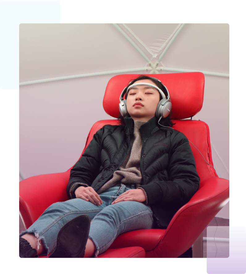 young woman is sitting in red chair with headphones and listening to music