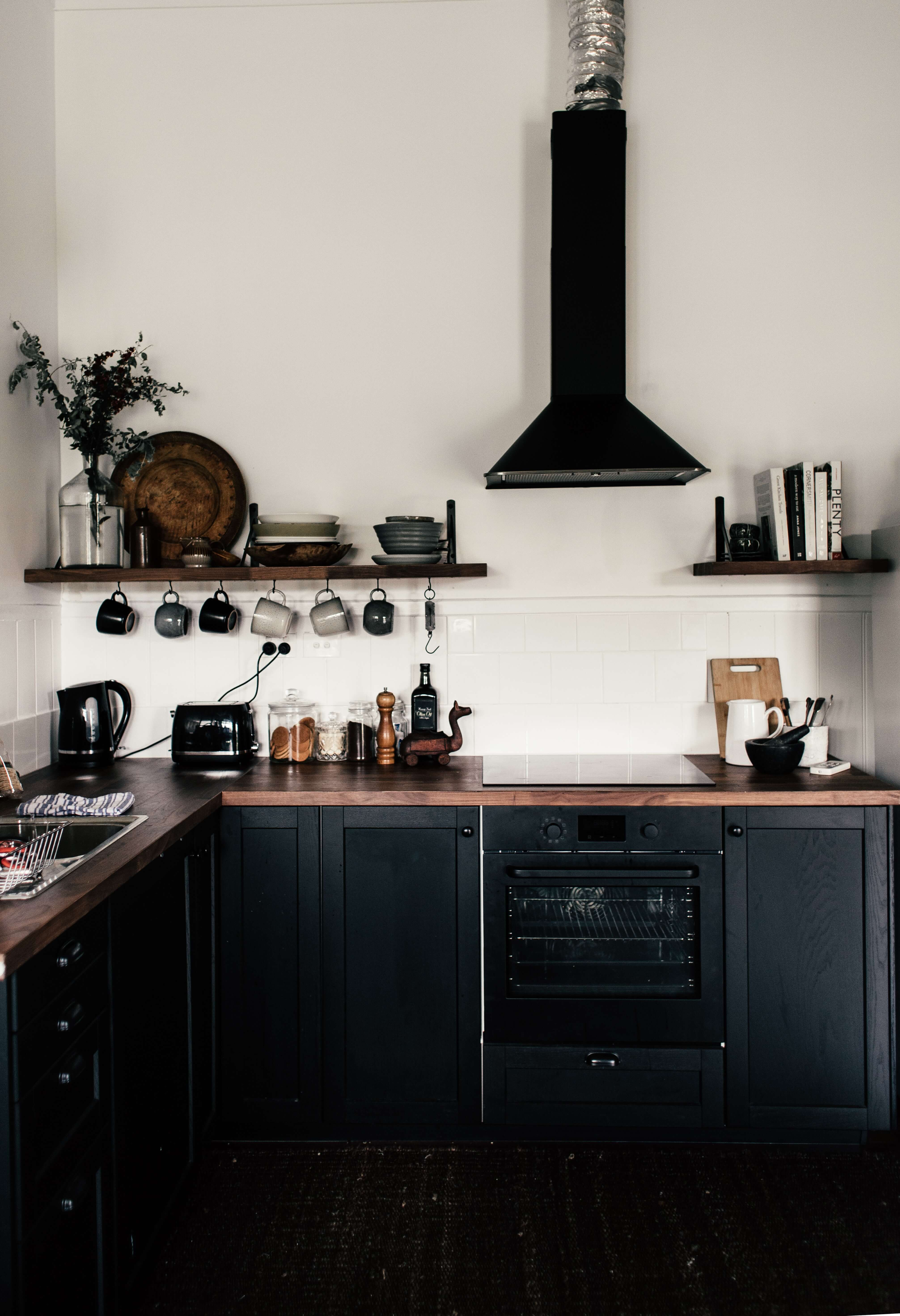 Kitchen with black finish and white tiles