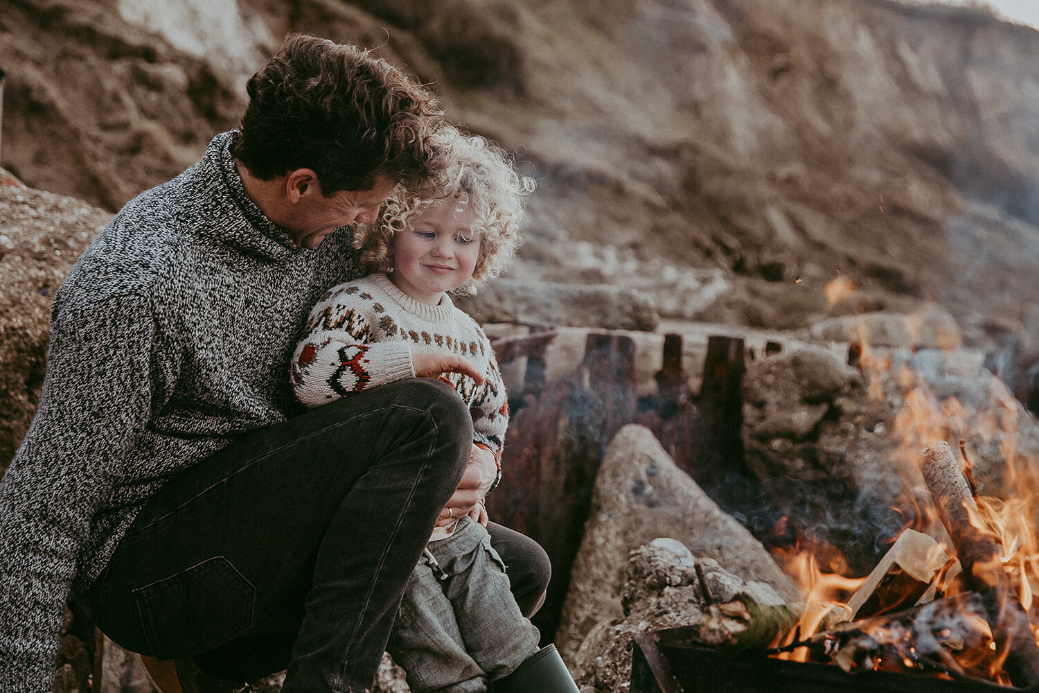 Father and son at a beach bonfire