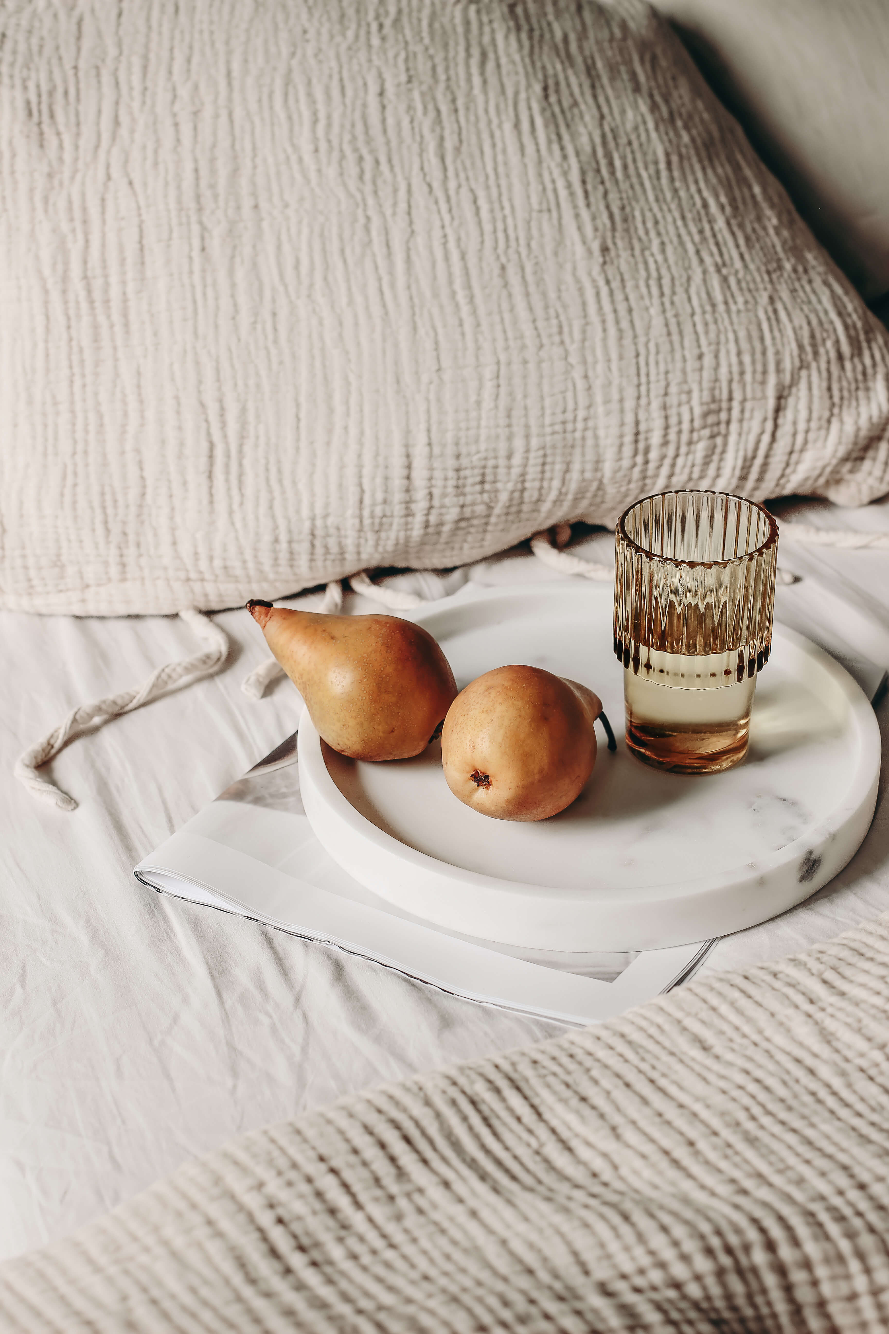 Pears and glass on a tray in bed