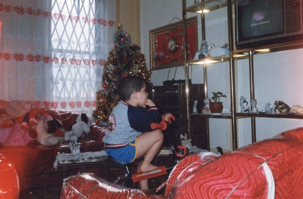 Me trying to watch cartoons. This photo screams 80's/90's. The plastic covered couches again, the shorts, the Christmas tree, the ceramic swan. Times were simple yet awesome.