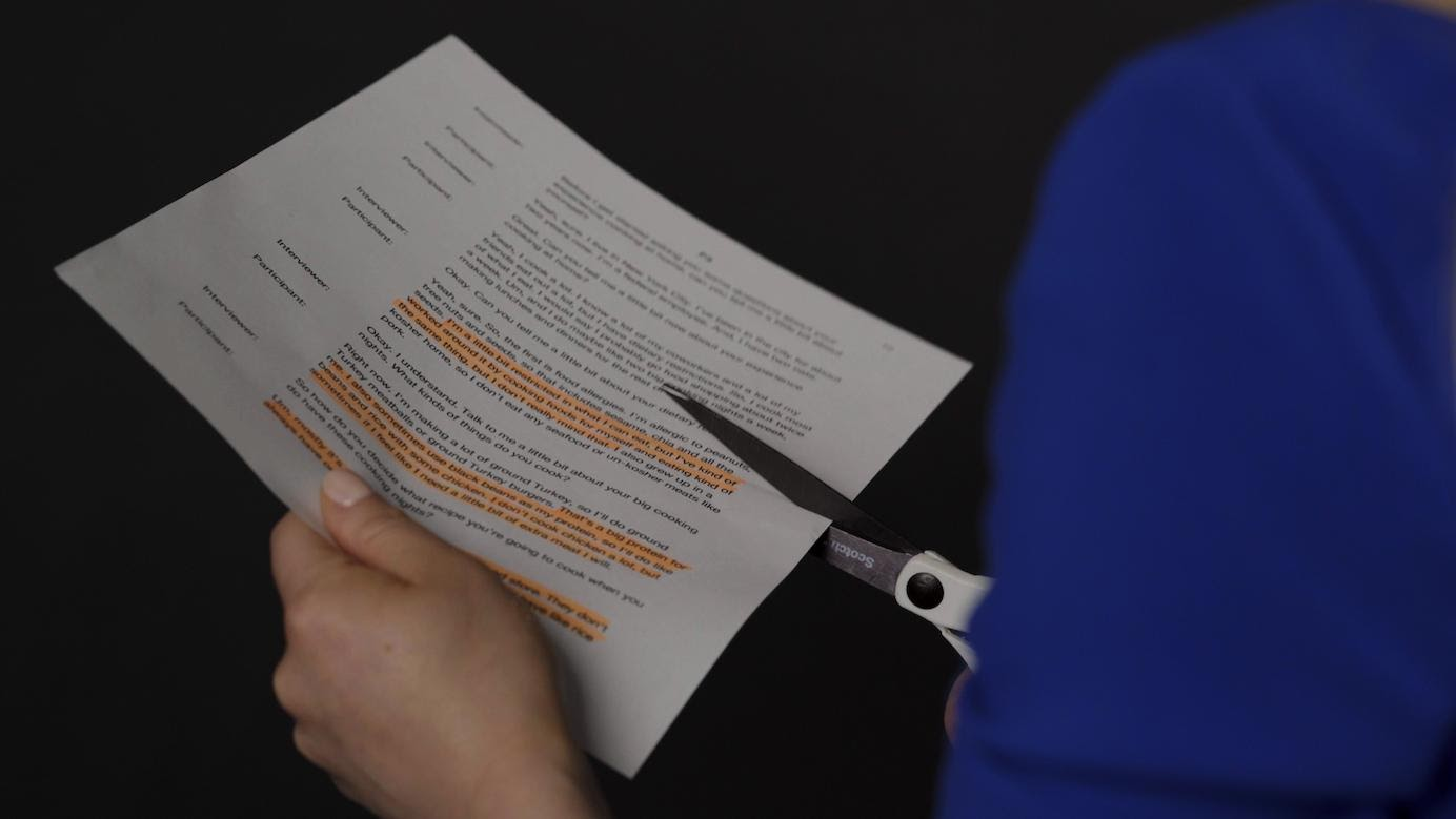 A photograph of a highlighted transcript being cut up into sections.