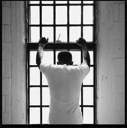 Imagen de un hombre desesperanzado, atrapado en un cuarto con unos barrotes