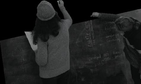 two people writing on a blackboard