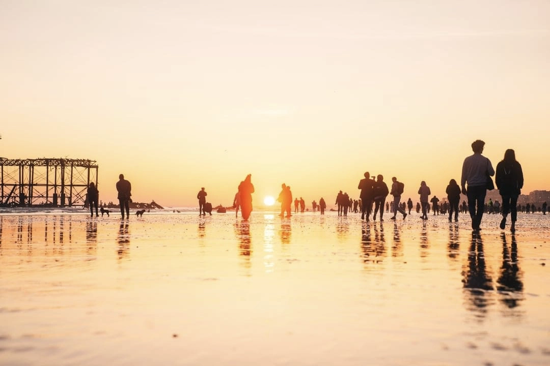People walking on a beach at sunset