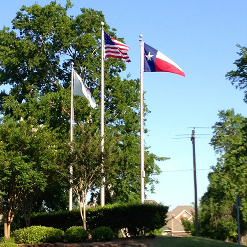 Three flagpoles at Independence Park in Pearland, Texas.