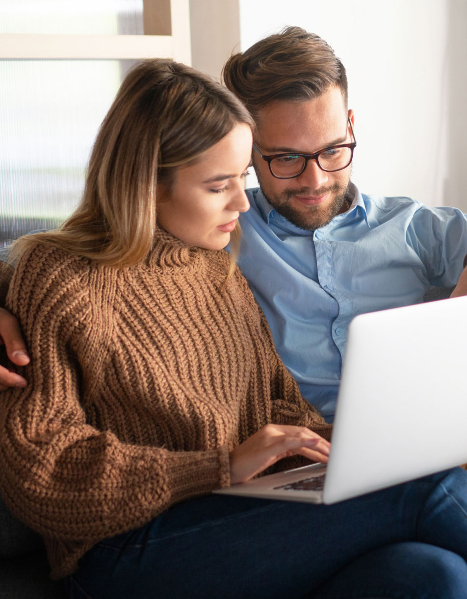 A young couple sitting on their couch looking at their laptop