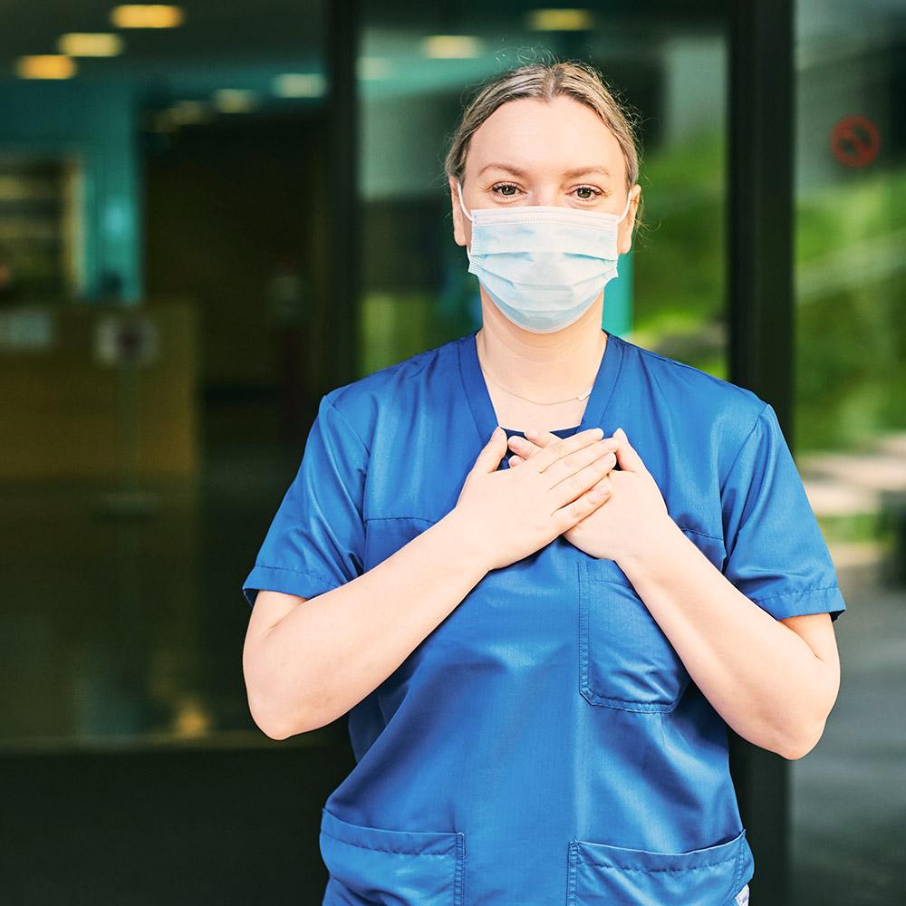 Nurse wearing PPE crossing hands