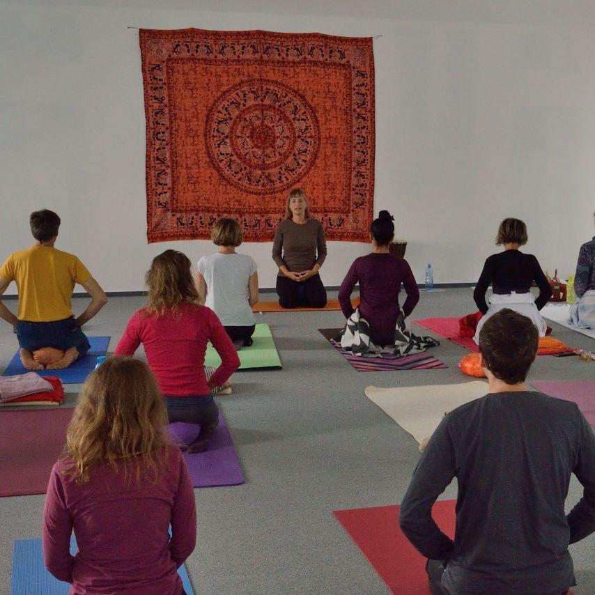 Lekce jógy vedená učitelkou sedící v sedu na patách.