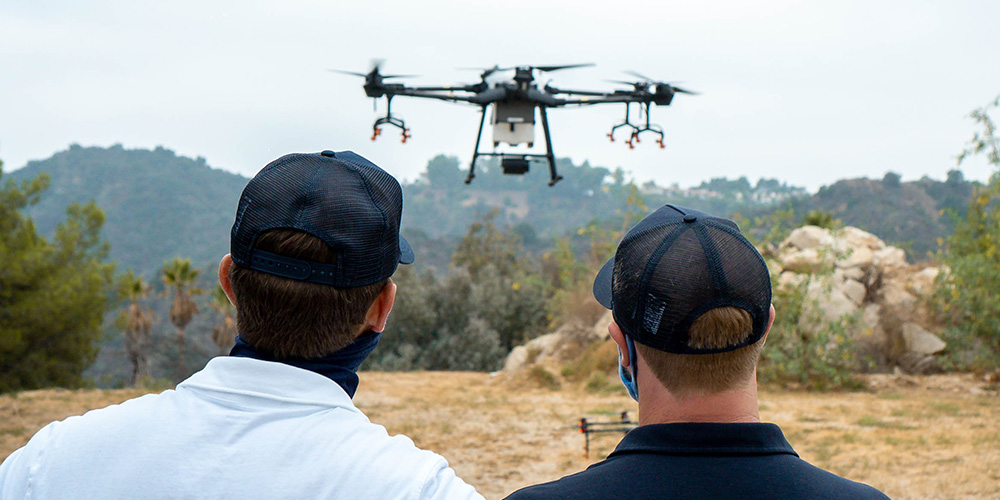 DragonFly UAS team members look on as a drone takes flight