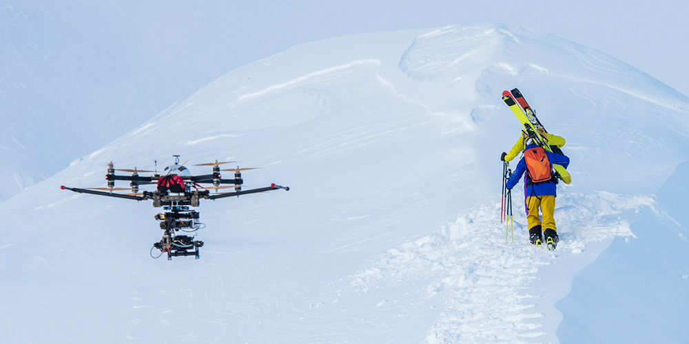Drone capturing footage of skiers ascending a mountain