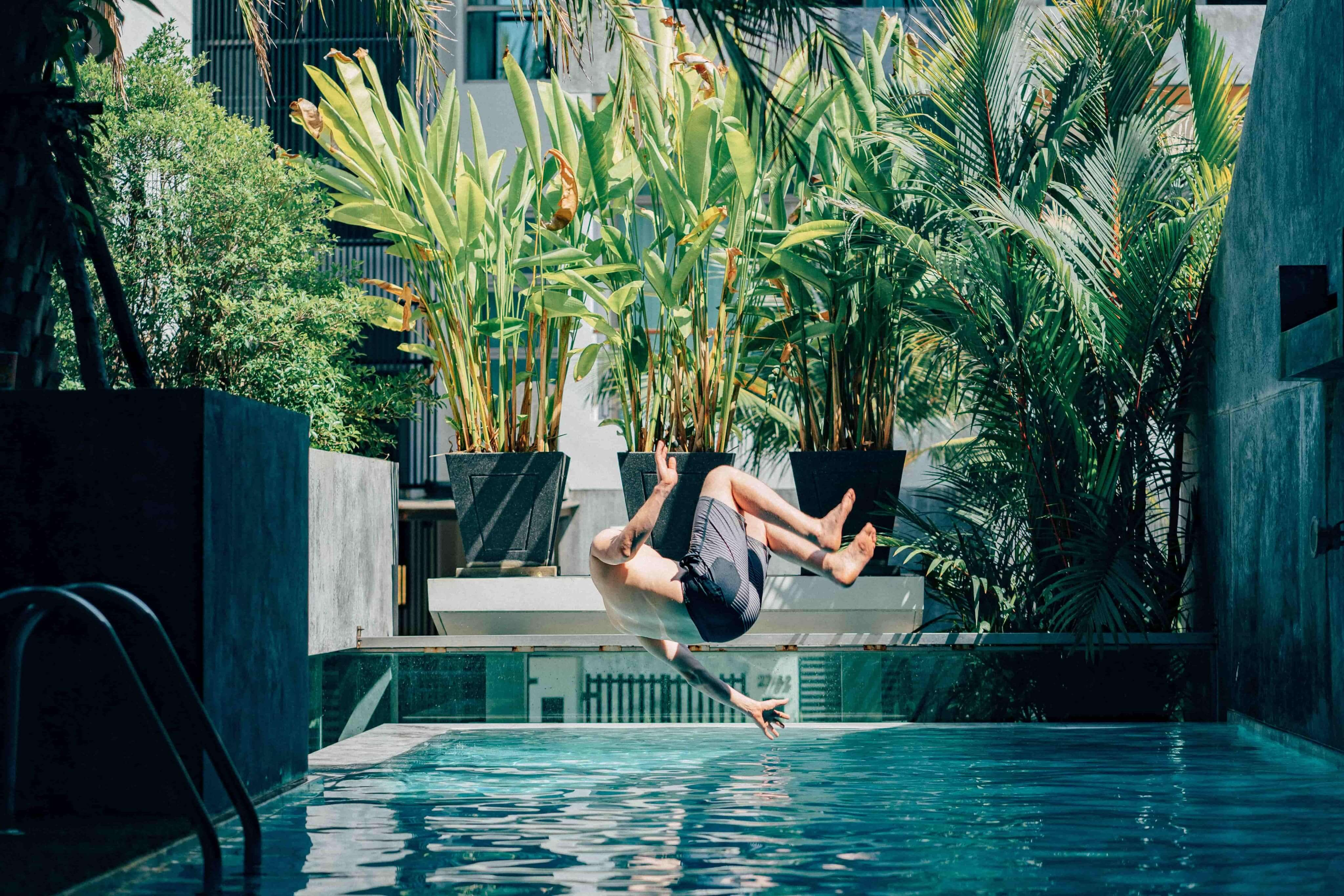 a person diving happily in to the clean and fresh pool