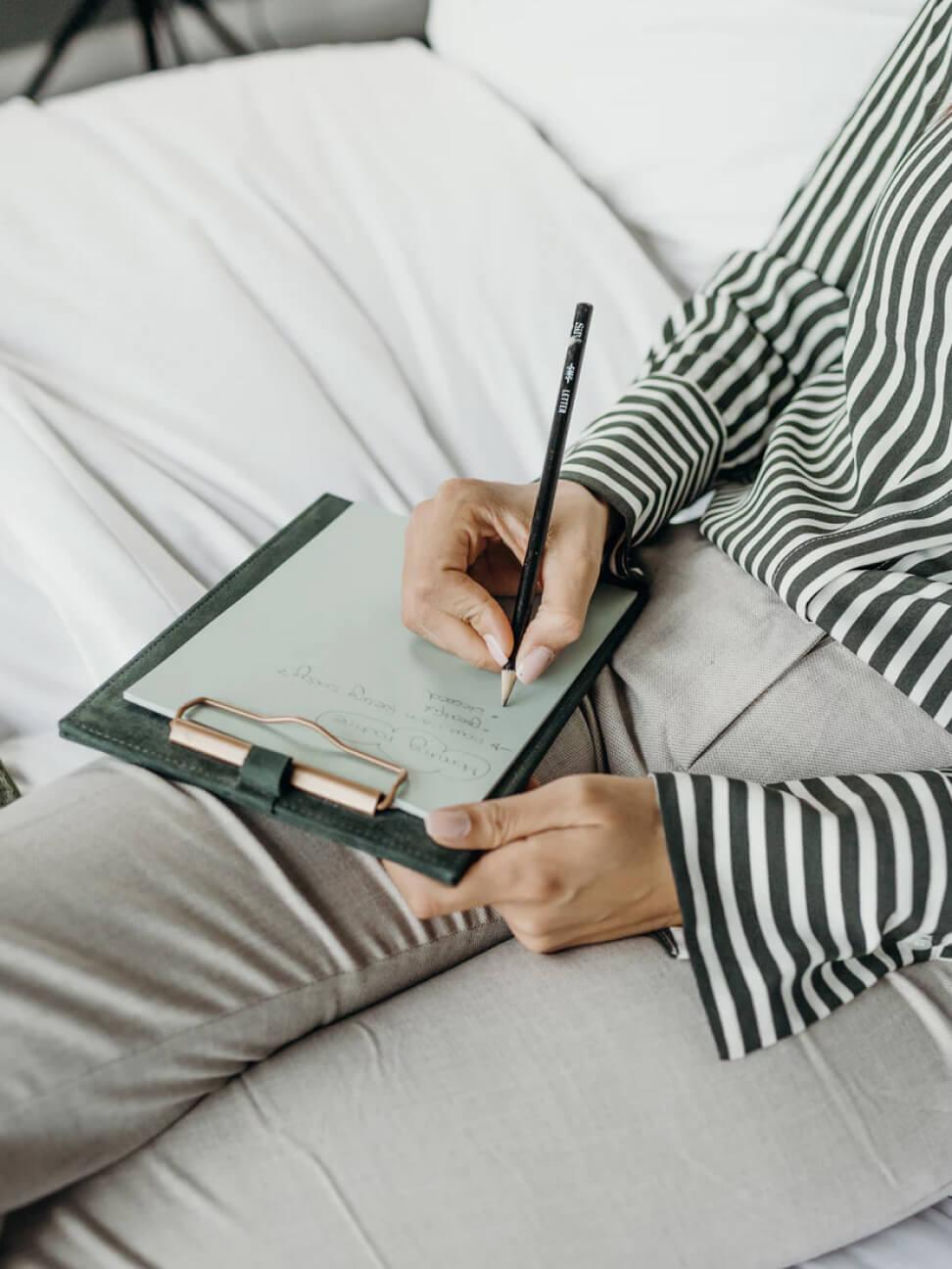 A women writing her Marketing plan, utilizing marketing strategies and tactics.