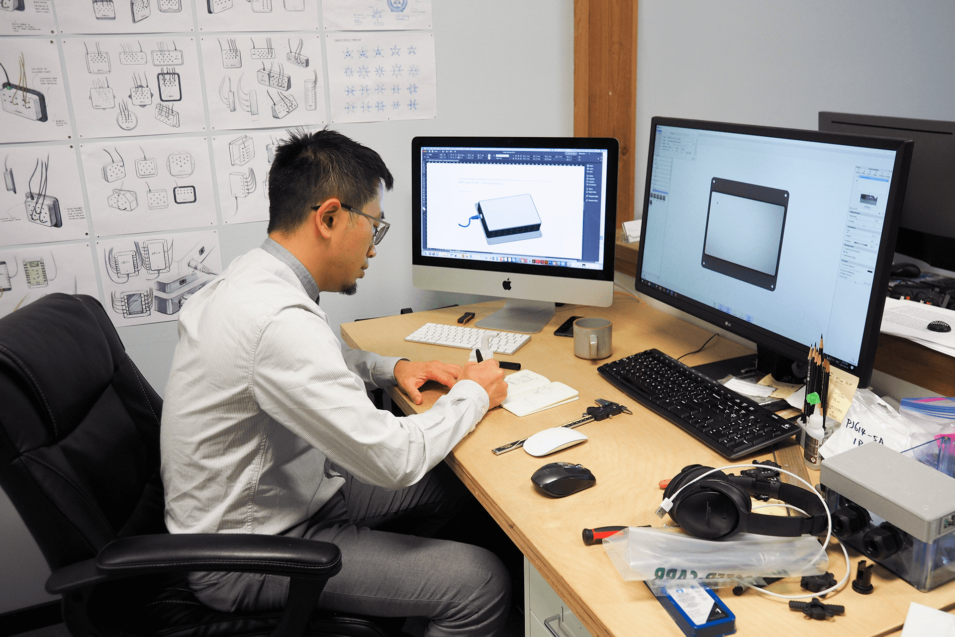 An industrial designer at their desk in front of their computer, sketching with pen and paper.