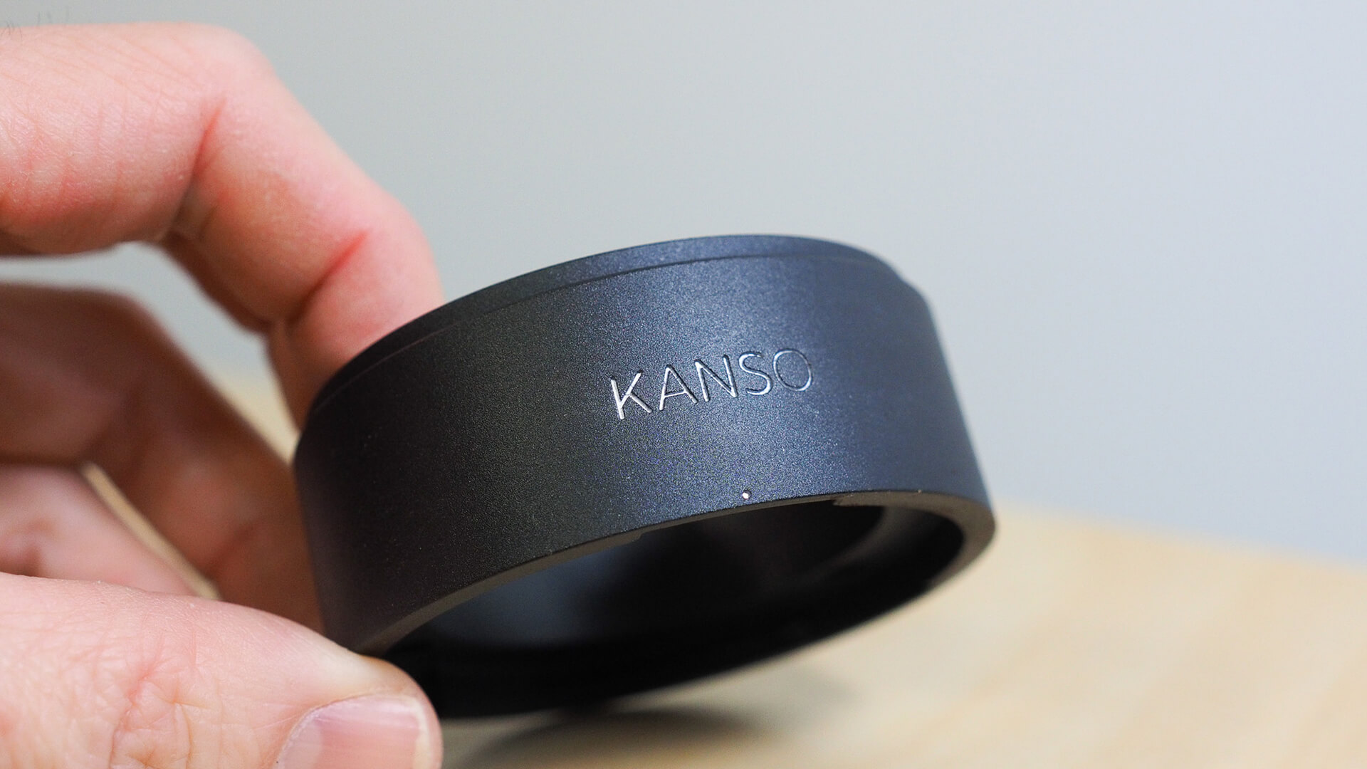 """A close up shot of someone holding up a prototype manufactured part of the HIKU hand coffee grinder, with the """"KANSO"""" logo prominently debossed on the surface."""