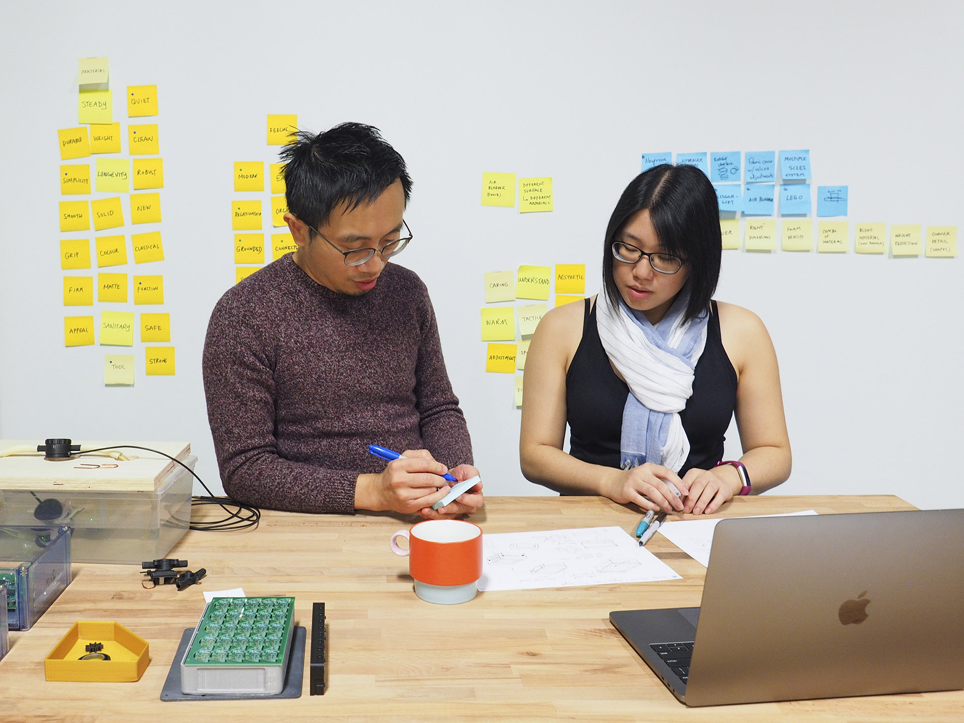 Two designers standing at a workbench, discussing and reviewing a set of sketches and prototypes.