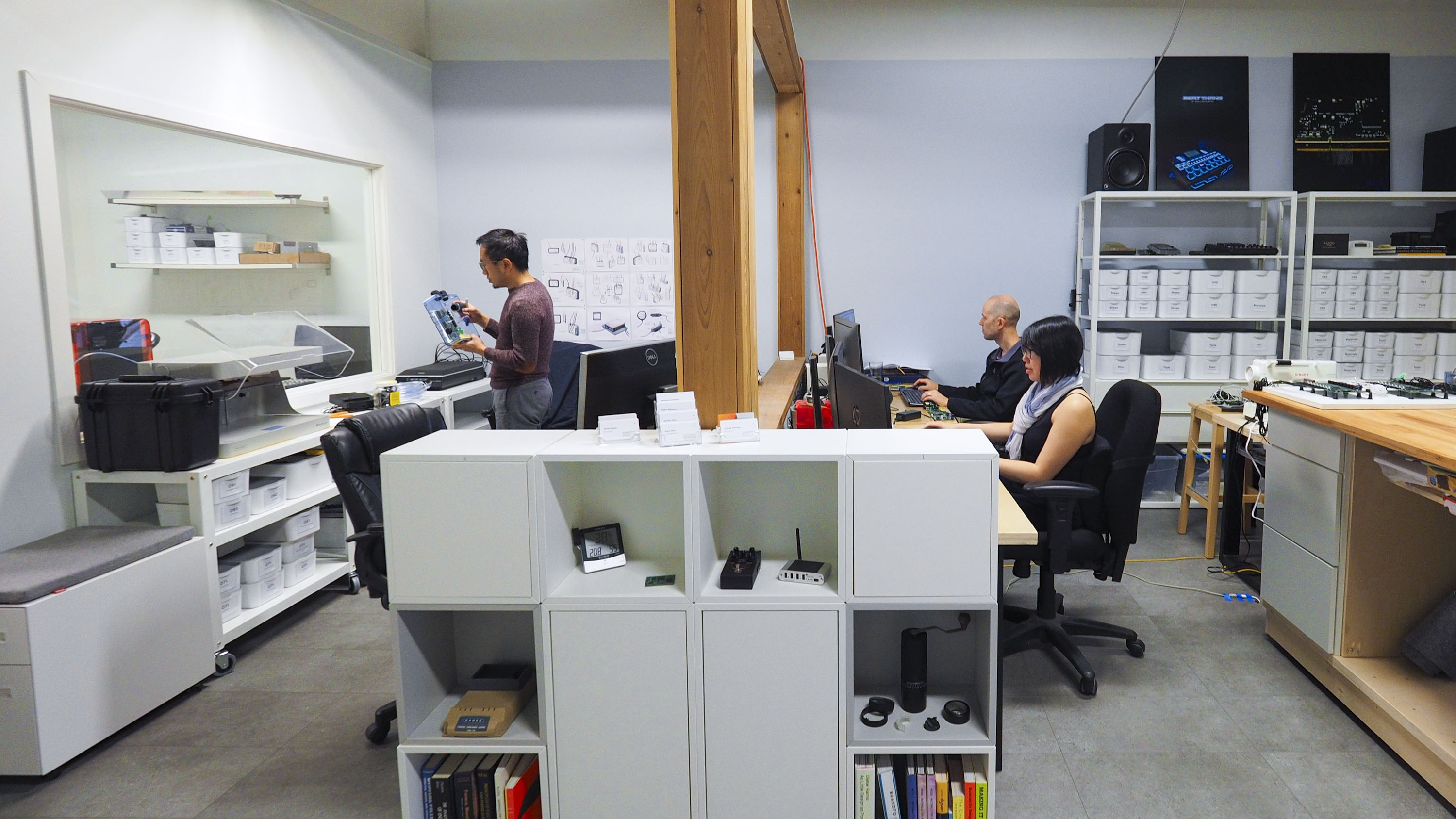 A wide angle photo of the office interior, with Altimus designers working on various projects.