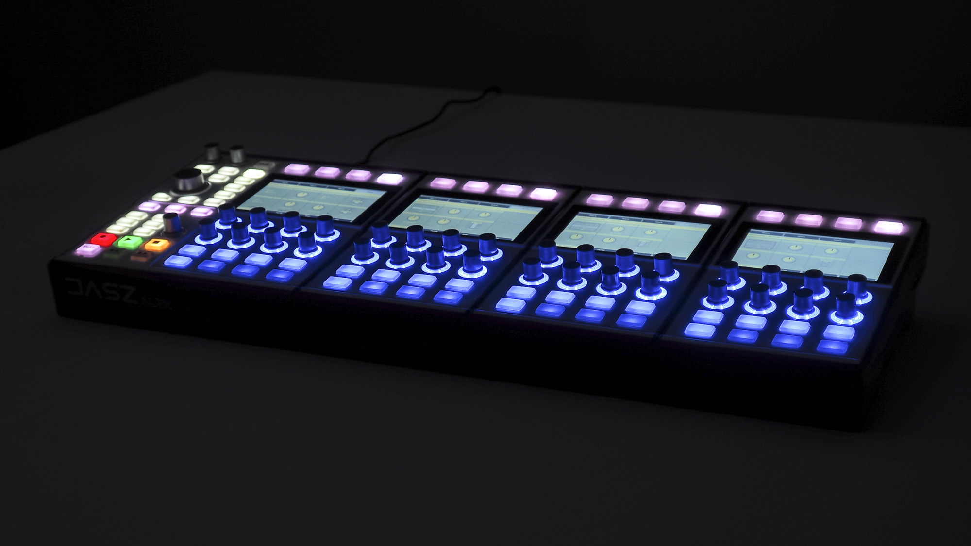 The DASZ ALEX Expandable Synthesizer in a QUAD formation, in a dark room with all its screens and buttons lit.
