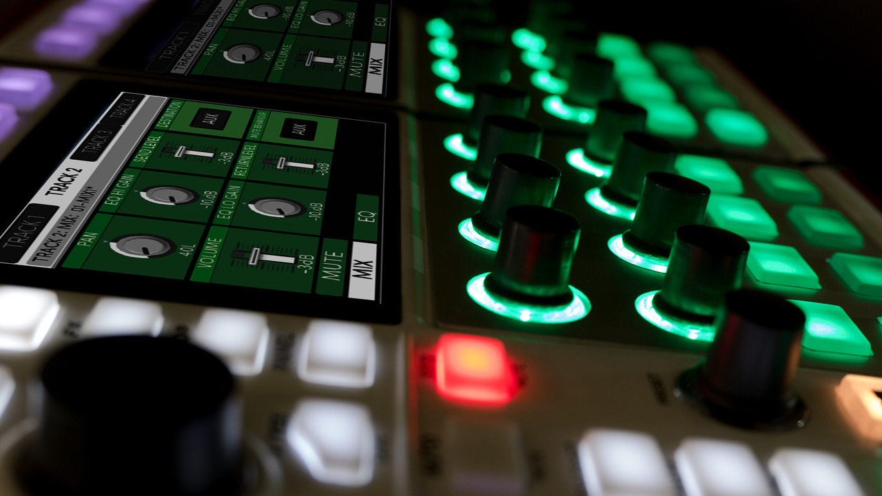 A close up side view of the DASZ ALEX Expandable Synthesizer in a dark room, with its screens and buttons lit.