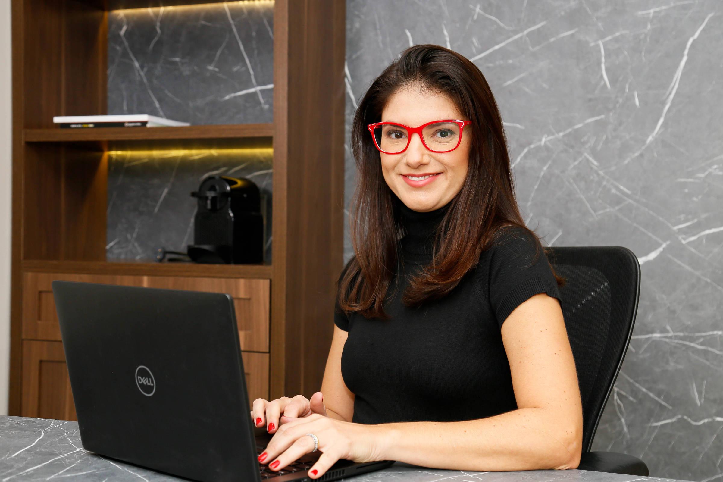 Uma mulher branca e de óculos vermelhos sentada diante de um notebook